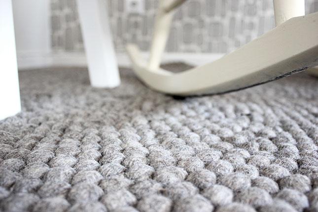 Schaukelstuhl im Arbeits- und Babyzimmer mit neuem Filzkugelteppich.