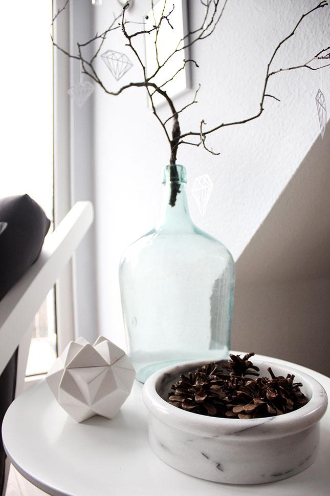 Winterdeko mit Kiefernzapfen und Zweig.